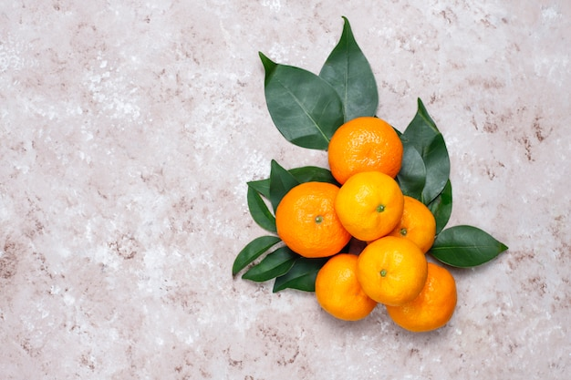 Mandarynki (pomarańcze, klementynki, owoce cytrusowe) z zielonymi liśćmi na betonowej powierzchni z miejsca kopiowania