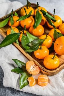 Mandarynki (pomarańcze, mandarynki, klementynki, owoce cytrusowe) z liśćmi w drewnianej misce. szare tło. widok z góry