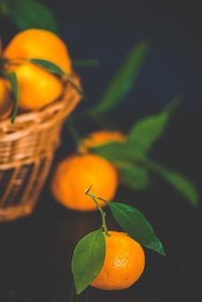 Mandarynki, pomarańcze, mandarynki, klementynki, owoce cytrusowe, z liśćmi w koszu na rustykalnym drewnianym ciemnym