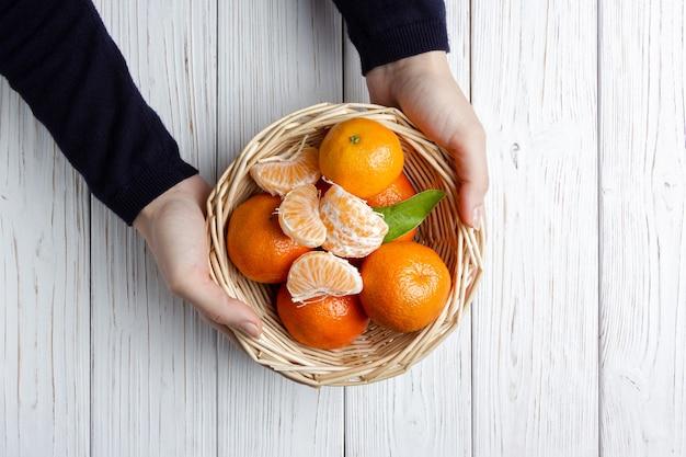 Mandarynki w koszu ze słomy na białym drewnianym stole. kobiece ręce trzymając świeże owoce. widok z góry świeżych mandarynek.