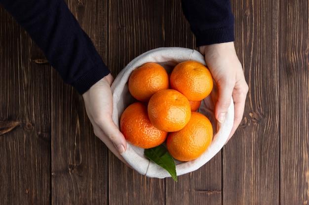 Mandarynki w koszu ze słomy na drewnianym stole. kobiece ręce trzymając owoce. widok z góry świeżych mandarynek.