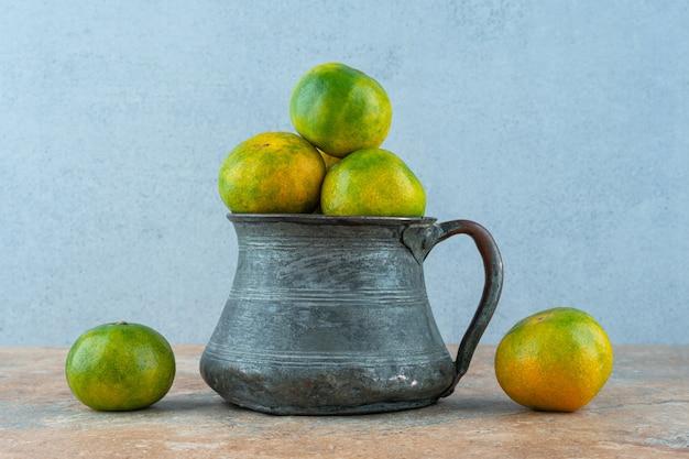 Mandarynki w metalowym naczyniu.