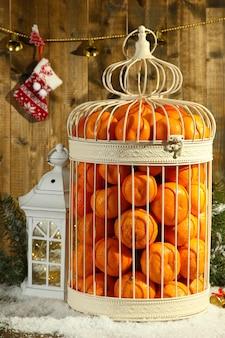 Mandarynki w ozdobnej klatce ze świątecznym wystrojem, na drewnianym tle