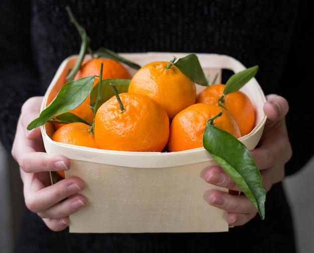 Mandarynki z liśćmi w drewnianym pudełku, człowiek z owocami, kobiece dłonie