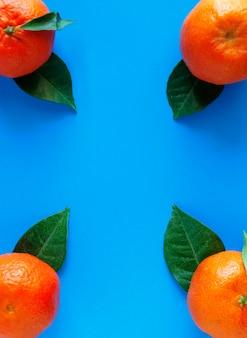 Mandarynki z zielonymi liśćmi po bokach na niebieskiej powierzchni.
