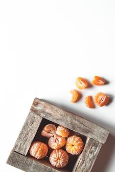 Mandarynki ze świeżych liści w drewnianym pudełku na białym tle na biały, widok z góry