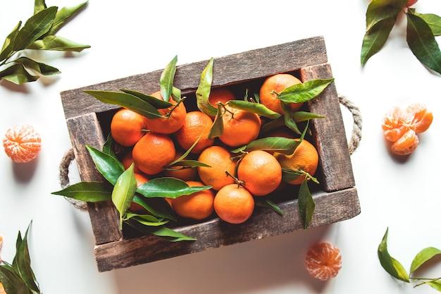 Mandarynki ze świeżymi liśćmi w drewnianym pudełku na białym tle, odizolowane na białym, górnym widoku