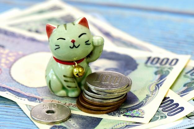 Maneki-neko, szczęśliwy kot i japońskie pieniądze.