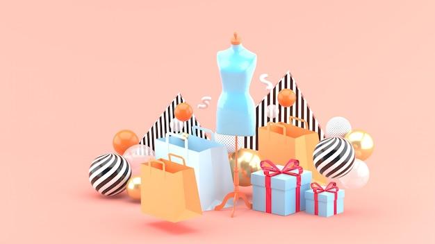 Manekin na środku torby na zakupy i pudełko na różowym tle