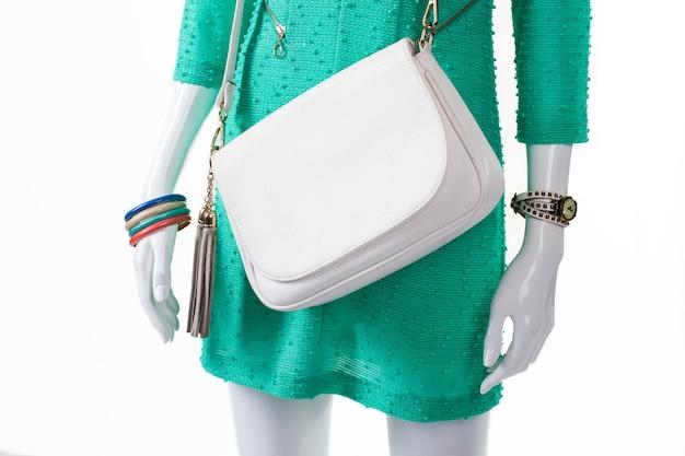 Manekin noszący zegarek i bransoletki. kolorowe bransoletki damskie z zegarkiem. turkusowa sukienka i biała torebka. gładka biała skórzana torebka.
