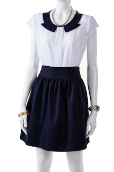 Manekin ubrany w bluzkę z krótkim rękawem. biała bluzka z granatowym kołnierzykiem. elegancka bluzka i dodatki na nadgarstki. lekki top i zegarek damski.