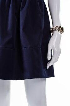Manekin ubrany w spódnicę i zegarek. granatowa spódnica z klasycznym zegarkiem. na wystawie malutki zegarek damski. akcesoria, które zawsze są w modzie.