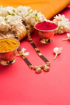 Mangalsutra lub złoty naszyjnik do noszenia przez zamężne hinduskie kobiety, ułożony z tradycyjnym sari z huldi kumkum i kwiatami mogra gajra, selektywne skupienie