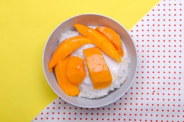 Mango lepki ryż w misce z kolorowym tłem