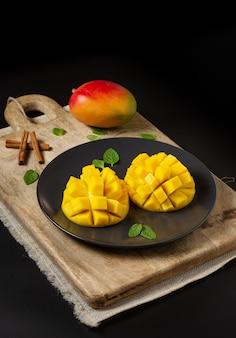 Mango pokroić na pół i pokroić w kostkę na drewnianej desce i całe mango, czarna powierzchnia z miejscem do kopiowania