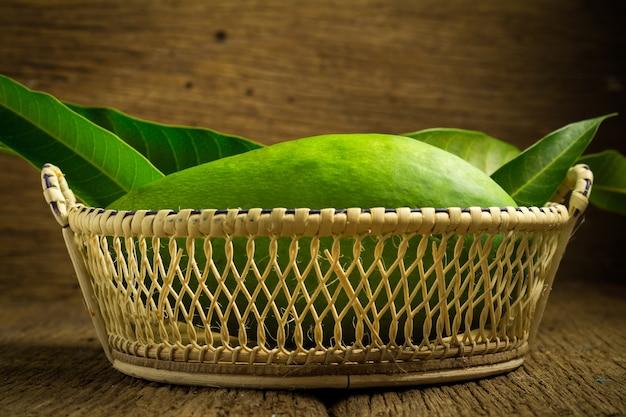 Mango zieleń w koszu na drewnie. azjatyckie. ranek