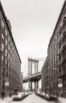 Manhattan bridge i empire state building widziane z brooklynu w nowym jorku. czarno-biały obraz z rozmytym pierwszym planem. stara stylizacja zdjęć, dodano ziarno filmu. stonowane w sepii