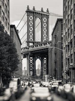 Manhattan bridge i empire state building widziane z brooklynu w nowym jorku. czarno-biały obraz z rozmytym pierwszym planem
