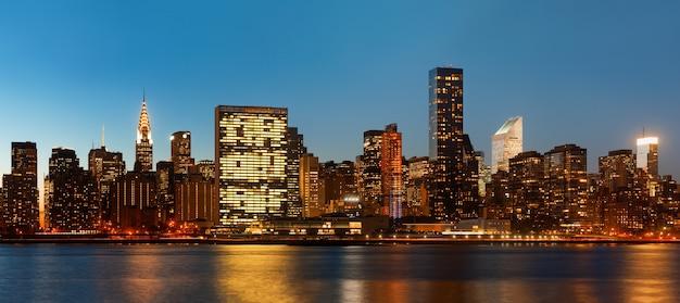 Manhattan. późnym wieczorem panorama panoramę nowego jorku ze światłami i odbiciami.