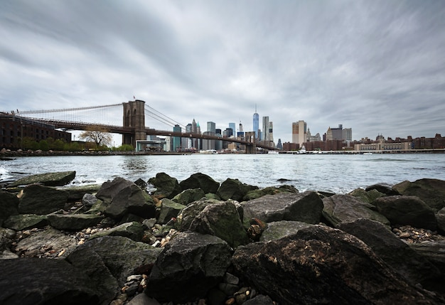 Manhattan skyline z brooklyn bridge. skały i kamienie na brzegu east river. panoramę manhattanu z dumbo