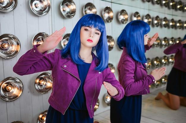 Maniak mody. portret syntetycznej dziewczyny glamour, fałszywa lalka z pustym spojrzeniem i niebieskimi włosami siedzi w studio. stylowa piękna kobieta w fioletowej kurtce w pobliżu żarówek i lustra.