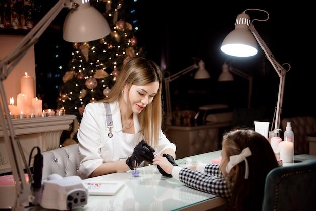 Manicure dla dziewczynki w salonie kosmetycznym.