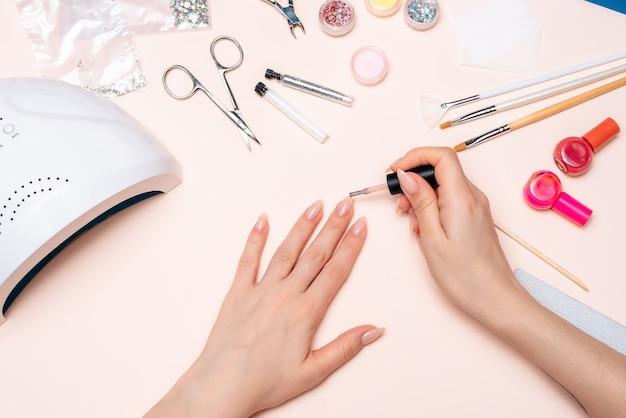 Manicure. dziewczyna maluje paznokcie. ręce z bliska