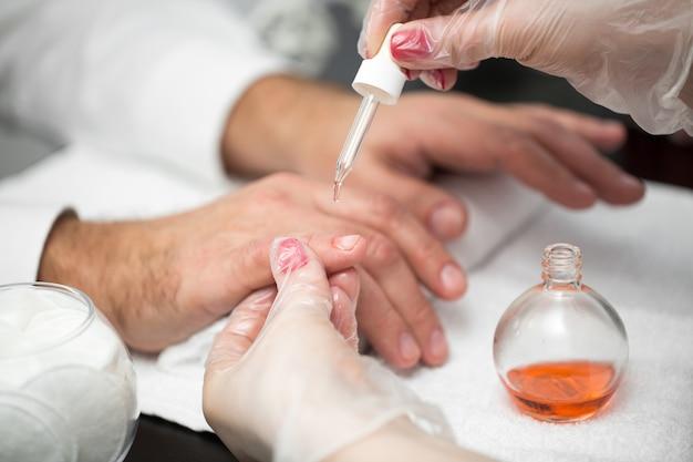 Manicure, hands spa olejek do skórek. piękny mężczyzna wręcza zbliżenie. wypielęgnowane paznokcie. ręce upiększające. zabieg upiększający.