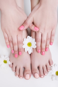 Manicure i pedicure nude na lato. kobiece dłonie i stopy na białym tle widok z góry. wynik zabiegu w salonie spa