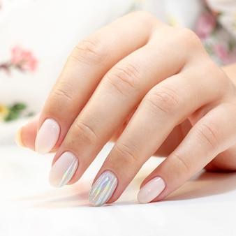 Manicure. manikiurzystka wykonała manicure i żel na paznokciach klientek w delikatnych odcieniach z paskami folii błyszczącej