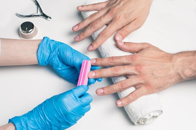 Manicure męski. kosmetolog w gumowych rękawicach pilnikuje paznokcie na męskich dłoniach.