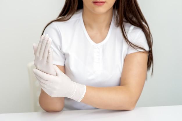 Manicure mistrz ręce zakładając gumowe rękawiczki.