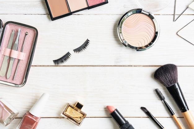 Manicure narzędzia i narzędzia w różowej skrzynce z gwoździa połyskiem, kosmetykiem i kobiet akcesoriami na białym drewnianym tle, odgórny widok, odbitkowy spce, piękna pojęcie.
