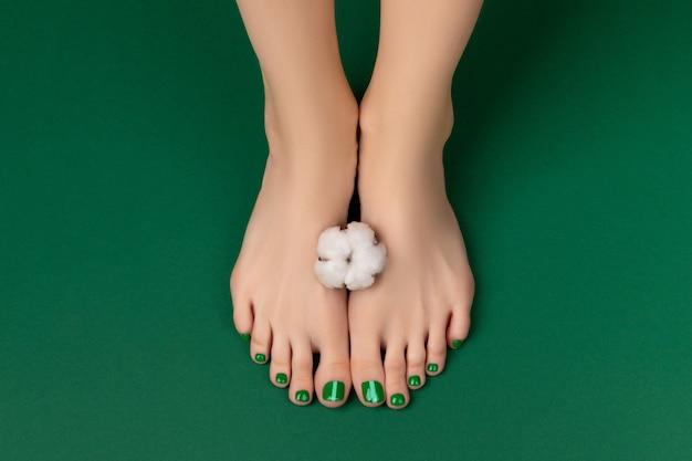 Manicure pedicure salon kosmetyczny koncepcja kobiece stopy z bawełnianym kwiatem