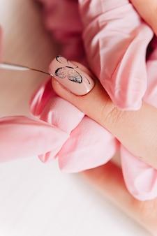 Manicure polegający na rysowaniu motyla na paznokciu cienkim pędzelkiem.