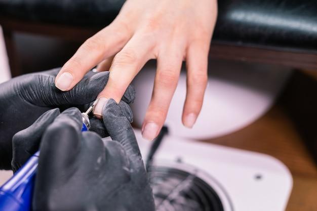 Manicure sprzętowy w salonie kosmetycznym. kobieta manikiurzystka stosuje wiertło elektryczne do paznokci