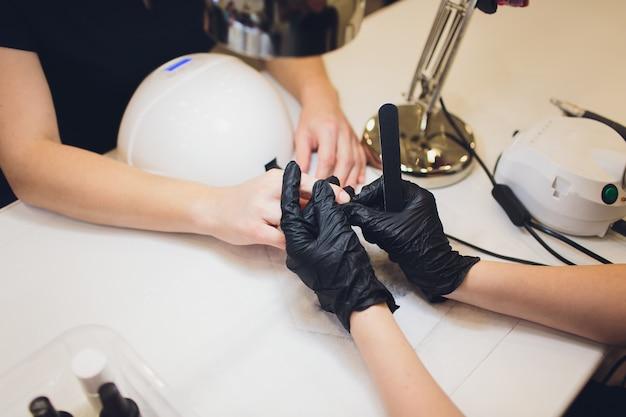 Manicure sprzętowy za pomocą urządzenia elektrycznego machine.ent. kobieta w salonie piękności.