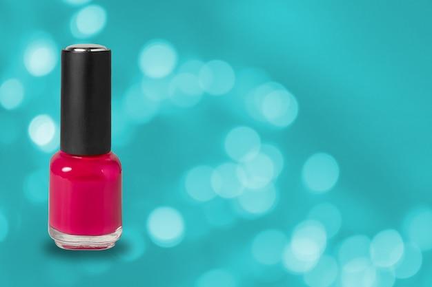 Manicure sztuki kosmetyka narzędzia, butelka czerwony kolorowy gel gwoździa połysk na błękitnym bokeh tle