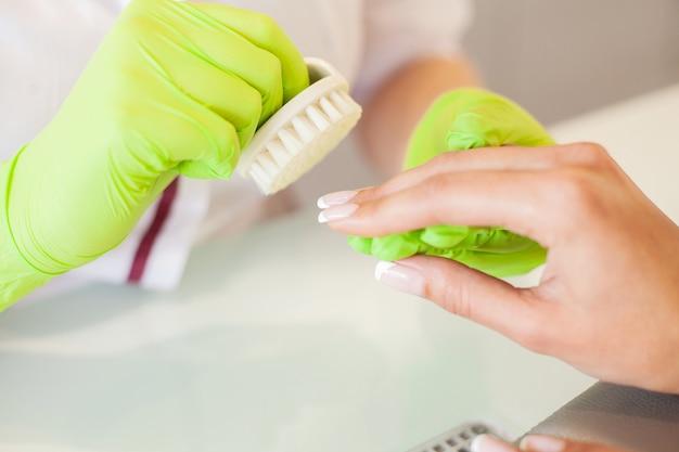 Manicure. umiejętny mistrz manicure trzyma kartotekę w jej rękach podczas gdy pracujący w jej piękno salonie