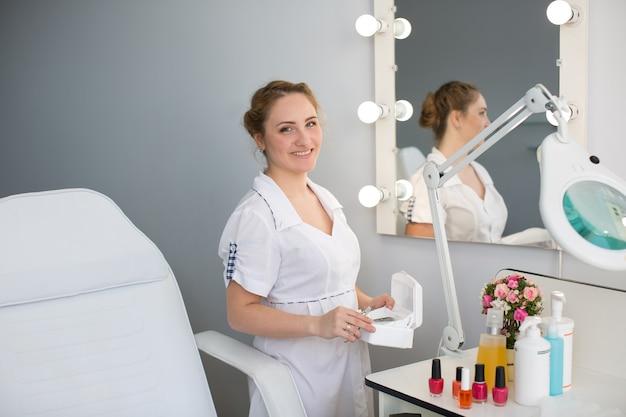Manicure w białej szacie trzymając w rękach instrumenty w gabinecie kosmetycznym.