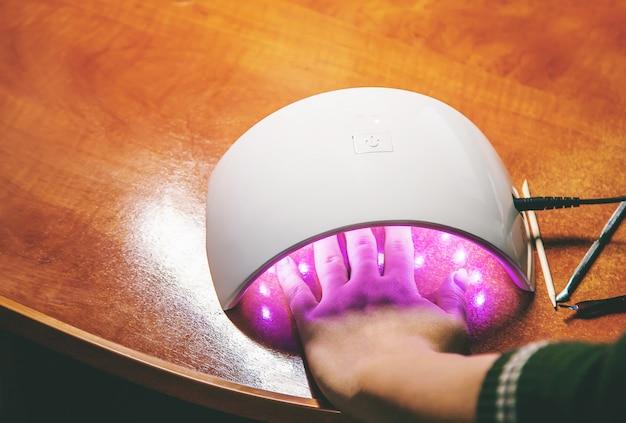 Manicure w domu, żelowy połysk, osuszony w lampie. selektywna ostrość.