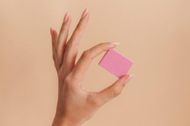 Manicure zdrowa pielęgnacja trzymając różowy pilnik do paznokci