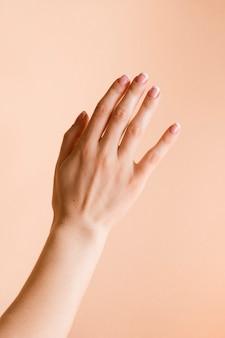 Manicured kobiety ręka na bladym pomarańczowym tle