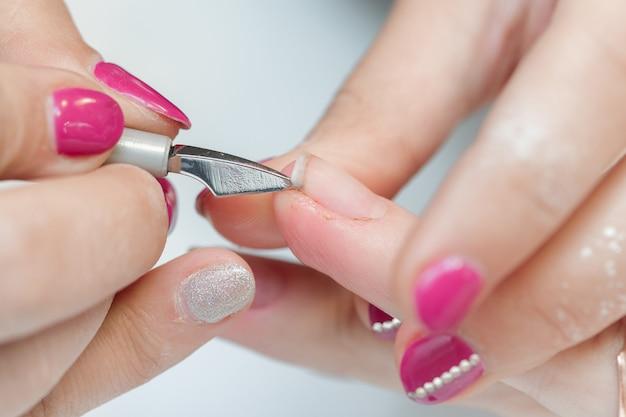 Manikiurzysta używa profesjonalnego narzędzia do manicure.