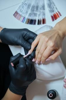 Manikiurzystka lakieruje paznokcie żelowe. profesjonalna pielęgnacja dłoni i paznokci w salonie kosmetycznym