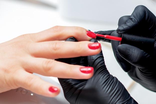 Manikiurzystka maluje paznokcie