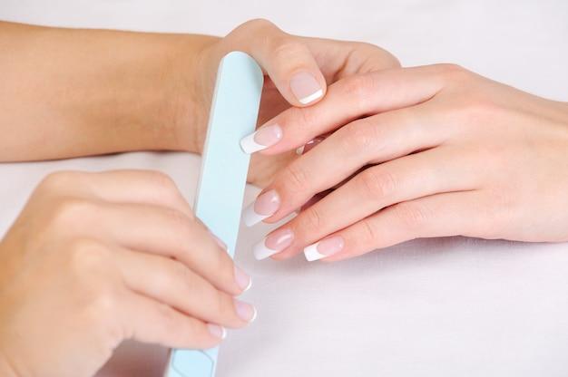 Manikiurzystka poleruje kobiece paznokcie francuskim manicure