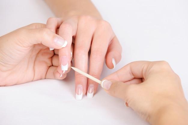 Manikiurzystka robi czyszczenie naskórka na kobiecych palcach kijem kosmetycznym