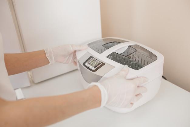 Manikiurzystka sterylizuje narzędzia w autoklawie lub piekarniku. mistrz w salonie przygotowuje jej instrumenty do dezynfekcji.