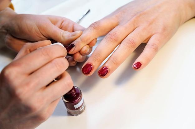 Manikiurzystka stosuje lakier do paznokci.